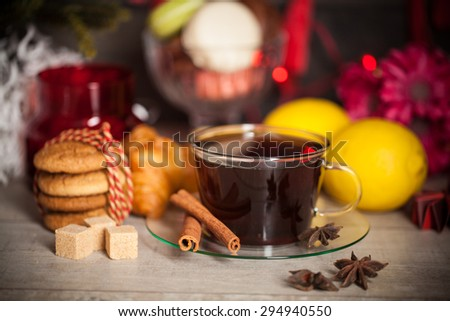 Christmas time, cup of tea with cinnamon and anise spices, festive decoration and candles on wood background. - stock photo
