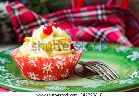 Christmas time decorations with festive decorated cupcake on the plate on rustic background