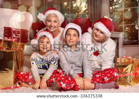 Christmas time. Happy family at home over christmas gifts. Boys with mother and grandmother smiling, posing in red santa claus hats. Happiness content.