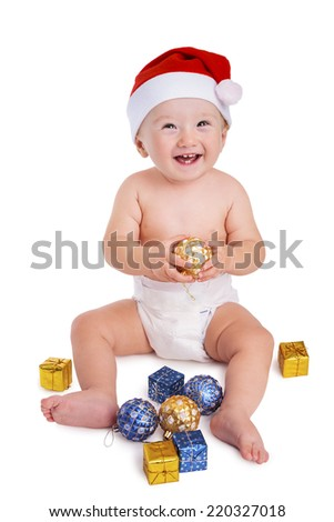 Christmas time: Little baby boy holding a bauble and wearing a red santa cap smiling and having fun with presents on the floor, isolated on white - stock photo