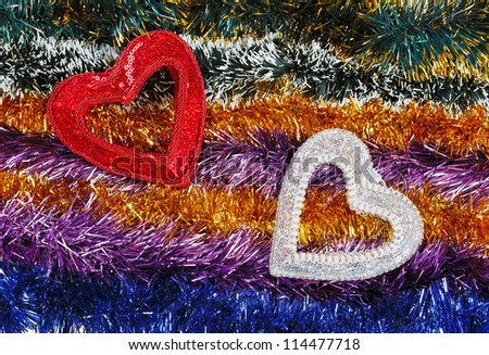 Christmas tinsel multicolored decoration with two hearts - stock photo