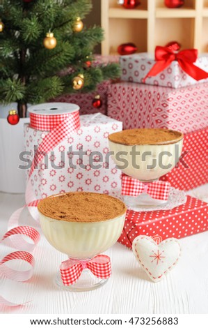 Christmas tiramisu in glass cups on the background of gift boxes and decorations