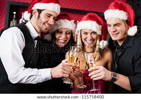 Christmas toasting party cheerful young friends with champagne at bar - stock photo