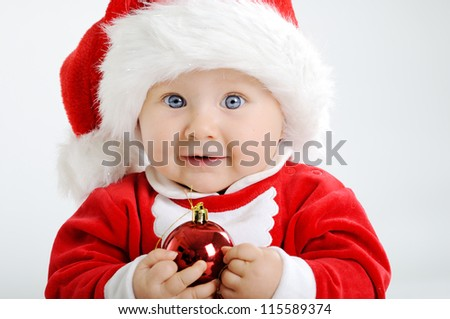 Christmas toddler in Santa hat holding a red bauble - stock photo