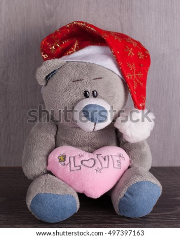 Christmas toy bear with santa hat on wooden background. The inscription on the heart, I love you