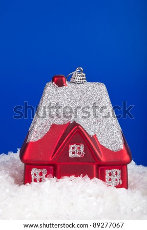 Christmas toy in the form of a small house on a blue background - stock photo