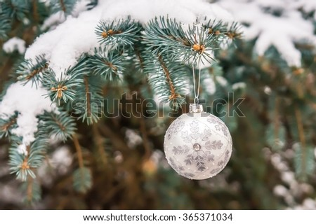 Christmas toy on a Christmas tree under snow, Christmas celebration concept - stock photo