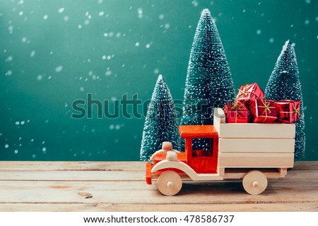 Christmas toy truck with gift boxes and pine tree on wooden table over green background