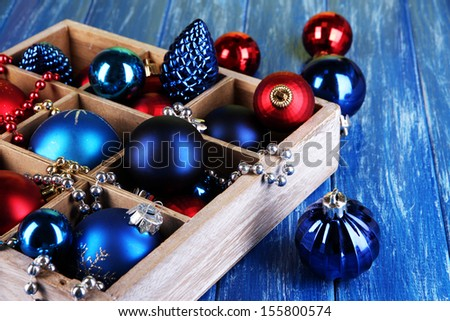 Christmas toys in box on wooden table close-up - stock photo