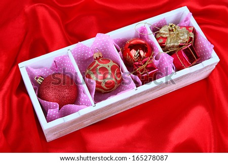 Christmas toys in wooden box on bright background