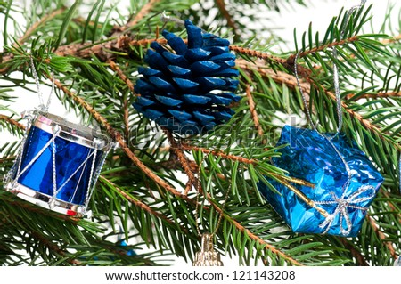 Christmas toys on a fir-tree branch isolated on white background