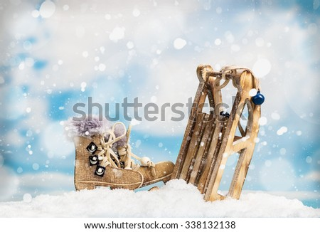 Christmas toys sleds and skates on the background of the sky with snow - stock photo