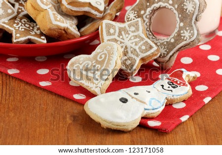 Christmas treats and glass of milk on wooden table close-up