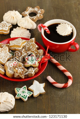 Christmas treats on plate and cup of coffe on wooden table close-up