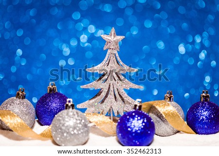 christmas tree and candy in snow on blue glitter background. studio shot
