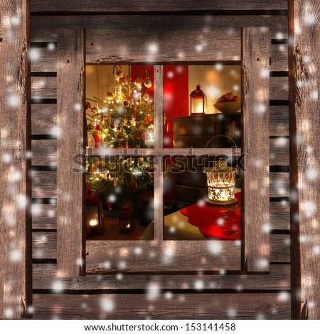Christmas tree and fireplace seen through a wooden cabin window - stock photo