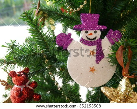 Christmas tree and happy of snow man toy with star glow  - stock photo
