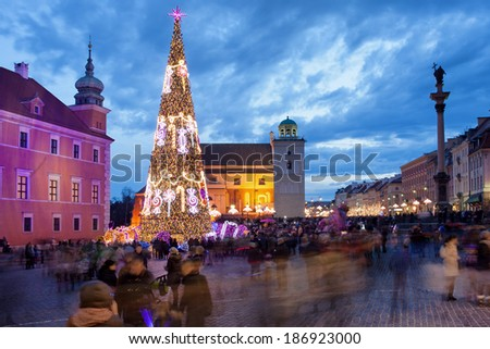 Christmas Tree and people on Castle Square in the Old Town of Warsaw, Poland, illuminated at dusk. - stock photo