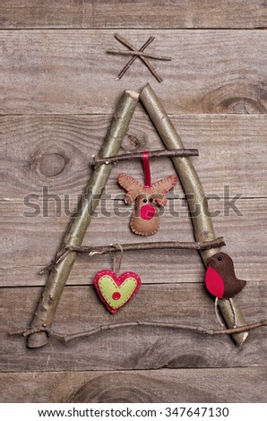 Christmas tree arranged from sticks, twigs, driftwood on wooden background. Handmade red and green heart, Rudolph reindeer and robin made from felt hanging on tree. Craft. - stock photo