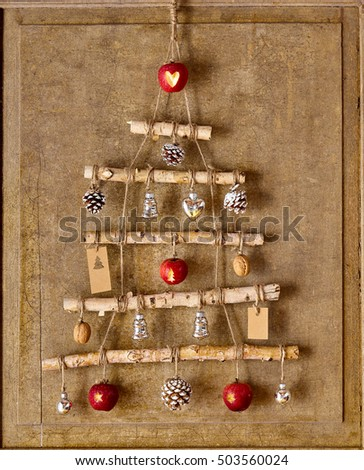 Christmas tree artwork made from natural objects connect by string and hanging from top of wooden board