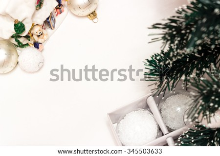 Christmas tree branch and Christmas balls of different colors on a white background