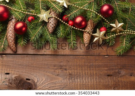 Christmas tree branch, cones, stars, balls on the background of wood