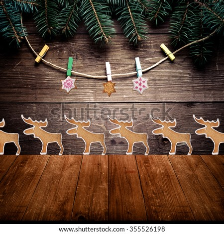 Christmas tree branch, gingerbread homemade cookies with icing and clothespins on rope on a wooden wall over old dark wooden table or board. New year theme. Collage. Space for text.