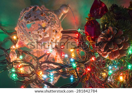 Christmas-tree branch pine cone candy Christmas tree toy ball and garland - stock photo