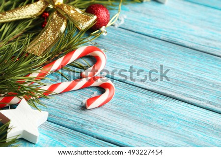 Christmas tree branch with baubles, candies on blue wooden table