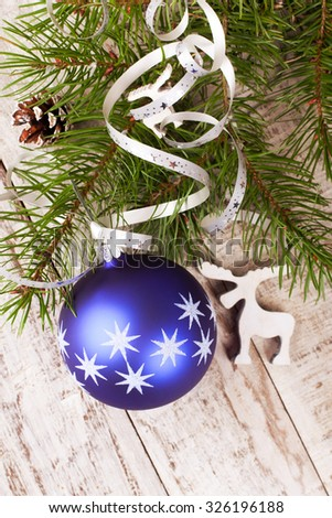 Christmas tree branch with blue christmas ball and decoration on old white wooden background. Christmas background with copy space for text. Seen from above.