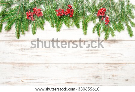 Christmas tree branch with red berries and falling snow. Winter holidays decoration - stock photo
