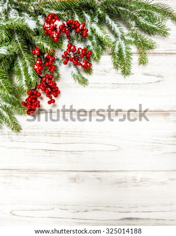 Christmas tree branch with red berries on wooden background. Winter holidays decoration - stock photo