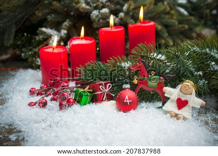 Christmas tree branches and candle for advent season four candles burning - stock photo