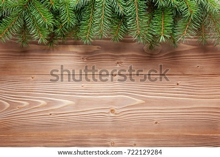 Christmas tree branches on wooden surface. Holiday background.
