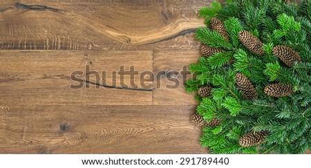 Christmas tree branches over rustic wooden background. green border from undecorated evergreen twigs - stock photo
