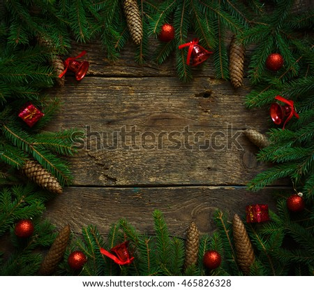 Christmas tree branches with cones and christmas decorations on wooden texture ready for your design. Winter holidays background