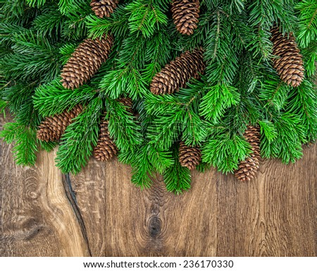 christmas tree branches with cones on wooden background. festive arrangement - stock photo