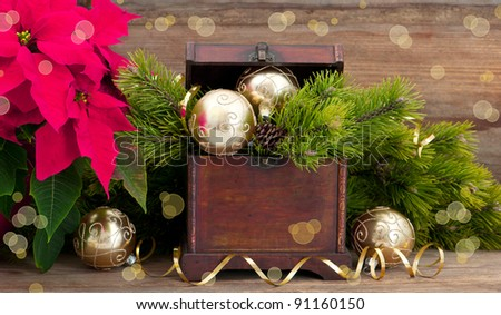 christmas tree brunch with golden decoration, vintage wooden box and pink christmas flower poinsettia