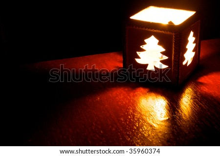 Christmas Tree candle on wooden table with black background - stock photo