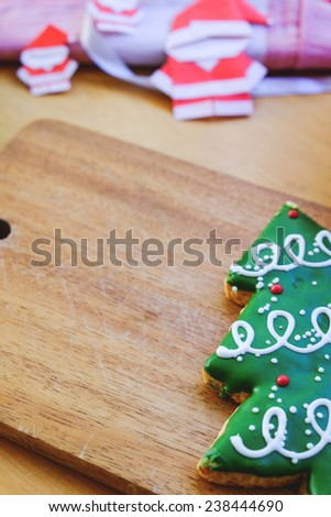 Christmas tree cookie and paper Santa on wooden plate. Christmas theme table - stock photo