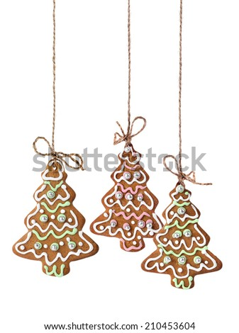 Christmas tree cookies hanging on a natural linen ribbon - stock photo