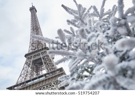 Christmas tree covered with snow near the Eiffel tower in Paris, France