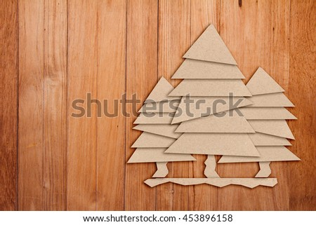 Christmas tree cut out from paper on a  light wooden texture background - stock photo