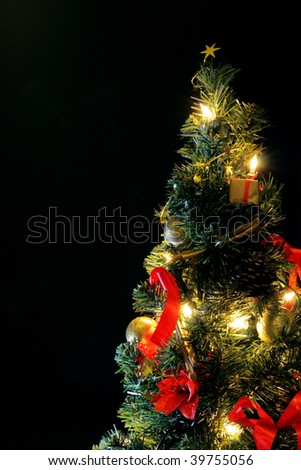 christmas tree decorated in red and gold with black background