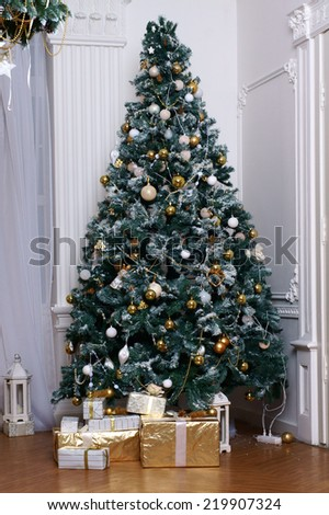 Christmas tree decorated with balls, toys and colorful ribbons with beautiful presents and gift boxes under it in festive home interior