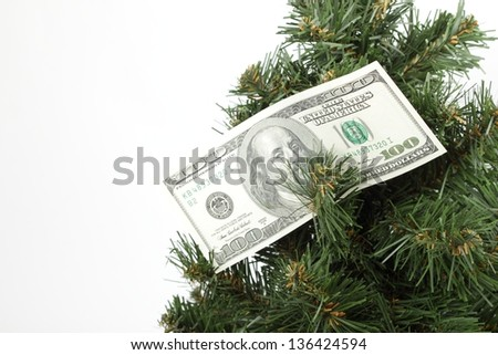 Christmas tree decorated with hundred dollar bills on white background on Holiday - stock photo