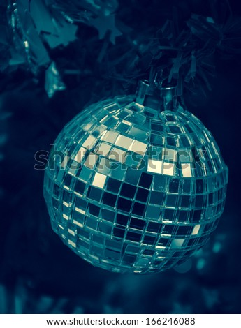Christmas tree decorated with mirror disco ball. Toned image. - stock photo