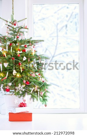 Christmas tree decorated with red and white traditional balls and lights with present boxes in a white living room next to a big window to a snowy garden - stock photo