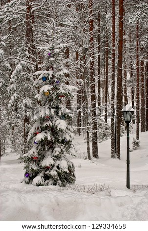 Christmas tree, decorated with toys in the winter forest. - stock photo