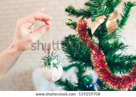 Christmas tree decorating with sparkling toy. Hand holding beautiful white decorative ball near pine tree with tinsel.